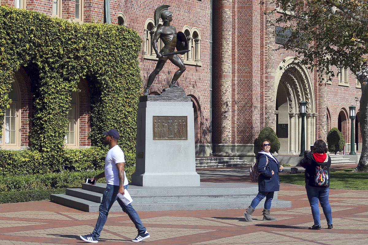 FILE - In this March 12, 2019 file photo, people pose for photos in front of the iconic Tommy Trojan statue on the campus of the University of Southern California in Los Angeles.