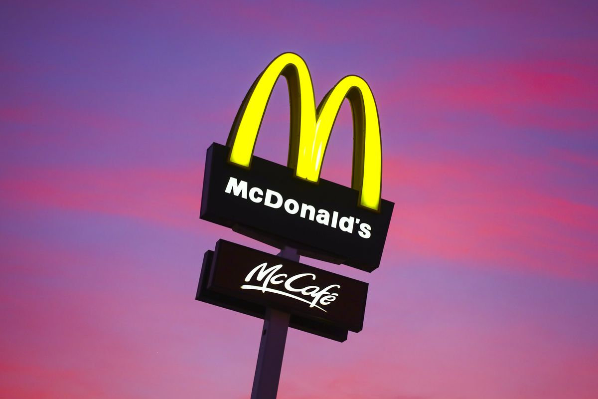 The McDonald's golden arches glow yellow against a pink and purple sky at sunset.