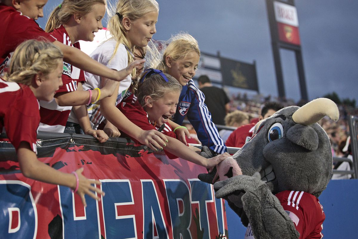 FRISCO, TX - APRIL 14:   FC Dallas fans celebrate with the Dallas mascot during the game against the Montreal Impact at FC Dallas Stadium on April 14, 2012 in Frisco, Texas.  Dallas defeated Montreal 2-1.  (Photo by Brett Deering/Getty Images)