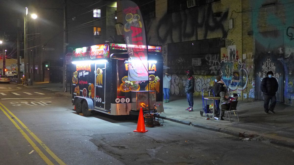 A black taco trailer in a pool of light, with darkened figures milling around.