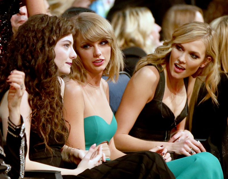 The three sit next to one another at the awards show.