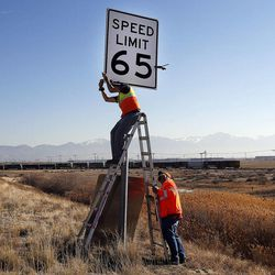Stephan Foster, top, and Jayson Kesler of UDOT remove a 65 mph sign to change it to 70 mph on I-80 west of Salt Lake City, Monday, Dec. 8, 2014.