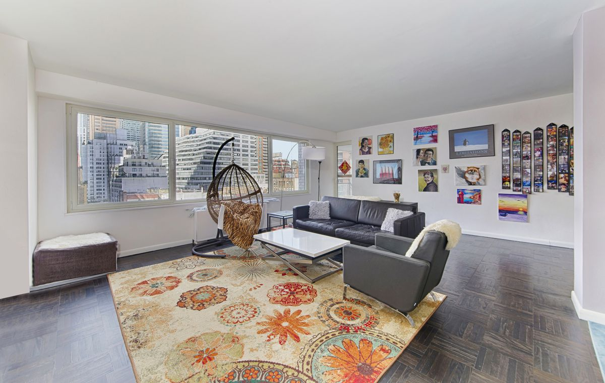 A living area with hardwood floors, large windows, a leather couch, and a colorful rug.