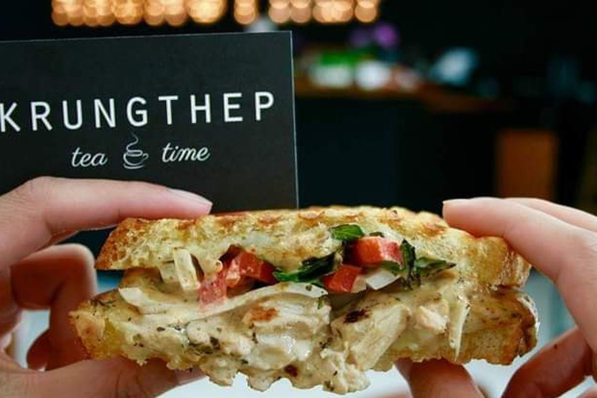 A hand holding a chicken salad sandwich loaded with mayo, parsley, chopped tomatoes.