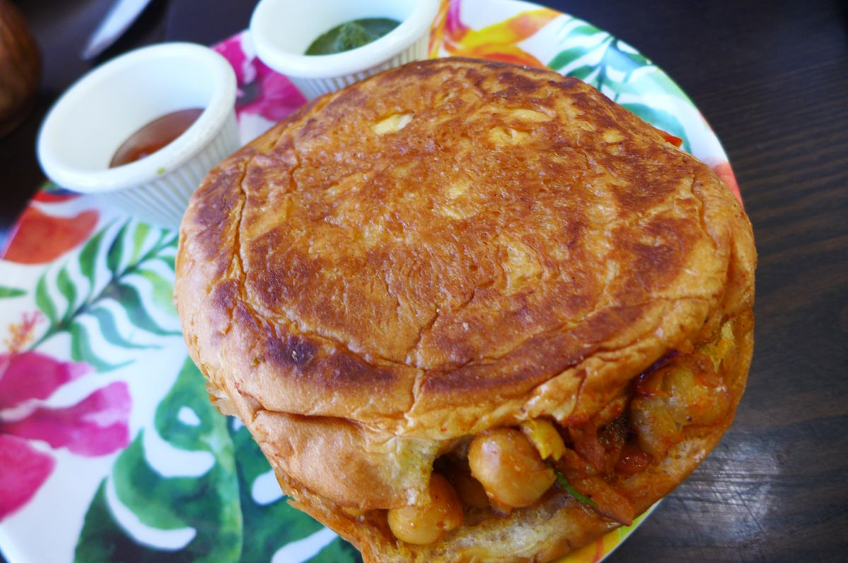 A roll like a hamburger bun with curried chickpeas tumbling out at the sides...