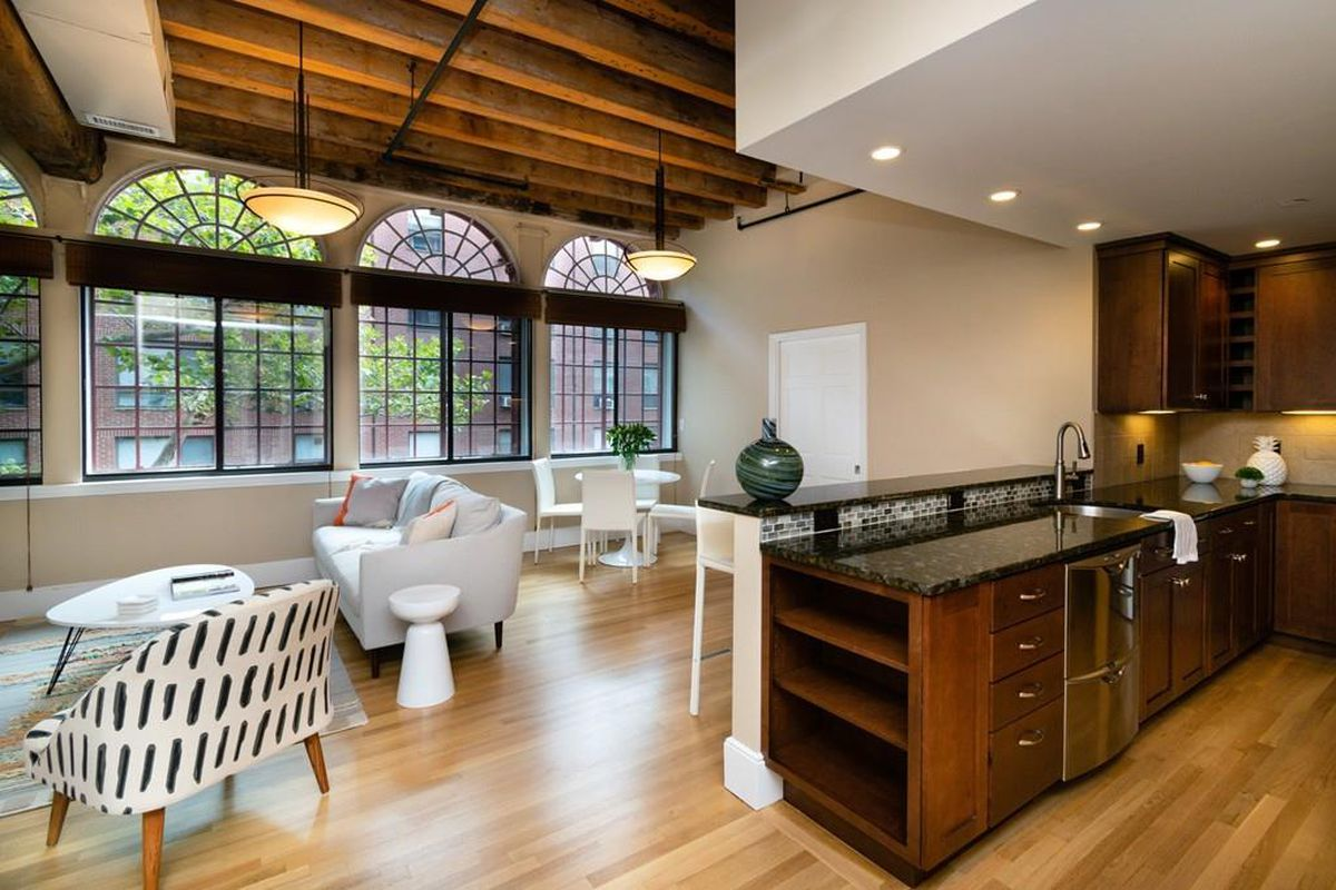 A cavernous living room-dining room area with a kitchen and massive arched windows.