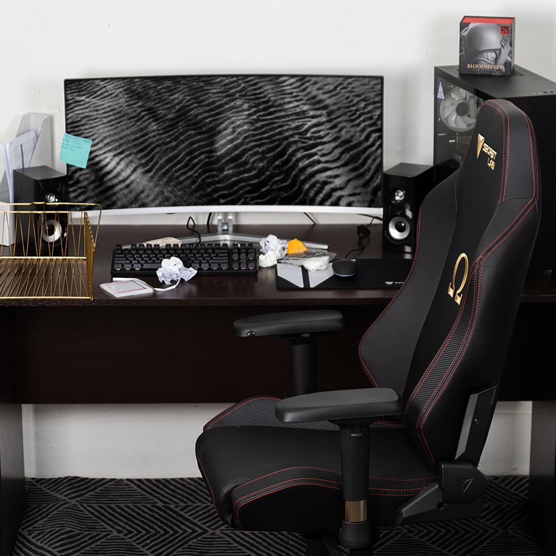 Secretlab Omega gaming chair in front of a cluttered desk