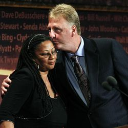 Former Boston Celtics player Larry Bird, right, kisses Donna Johnson, widow of basketball Hall of Fame inductee Dennis Johnson, after Dennis Johnson was inducted posthumously during enshrinement ceremonies in Springfield, Mass., Friday.