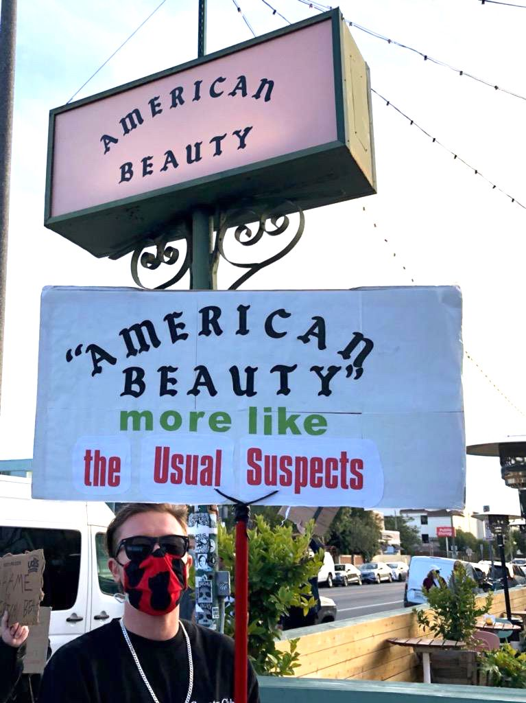"""An American Beauty server protesting outside the Venice restaurant on March 19, 2021 holding a sign that says """"American Beauty. More like The Usual Suspects."""""""