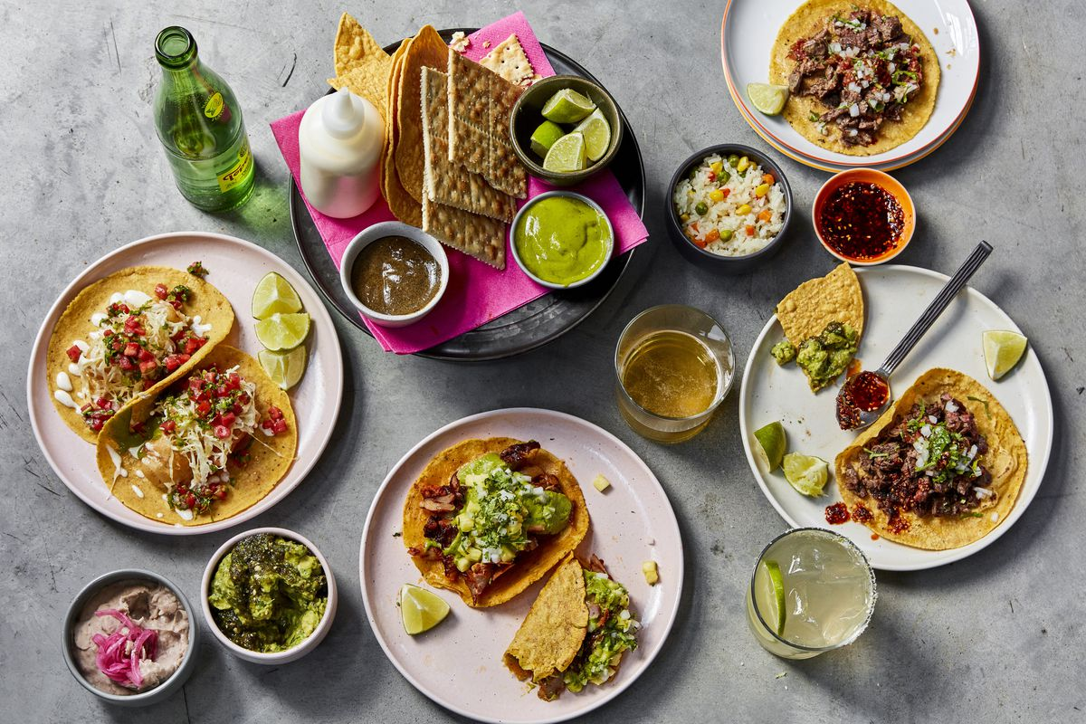 A platter of several tacos, mixed drinks, sauces, and Saltines crackers with limes and salt.