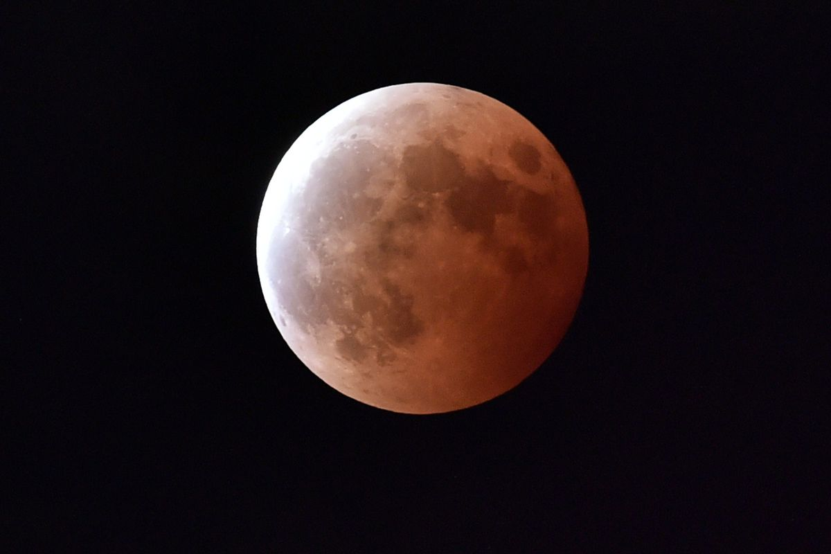 """The lunar eclipse — nicknamed a """"blood moon"""" — as seen from Tokyo, Japan."""