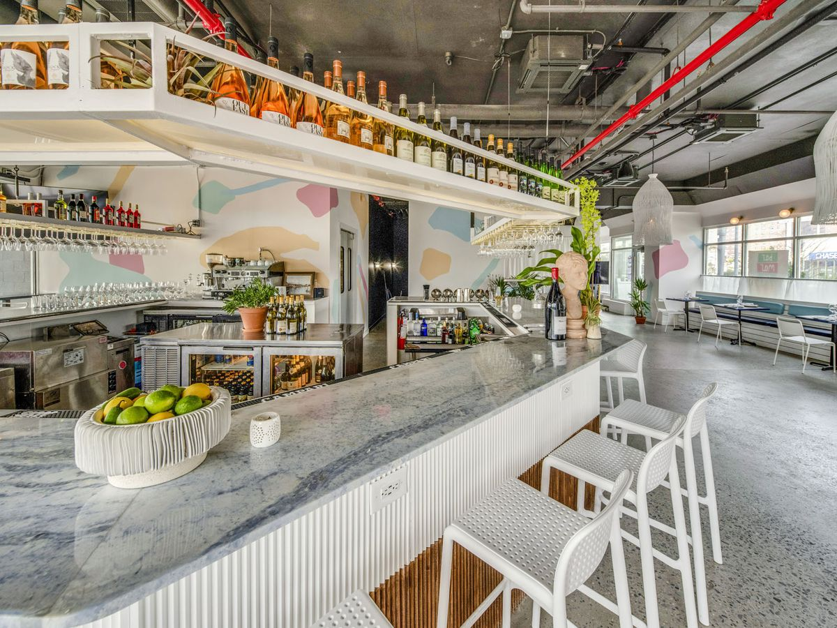 Inside a restaurant with stools set up against a white bar counter space