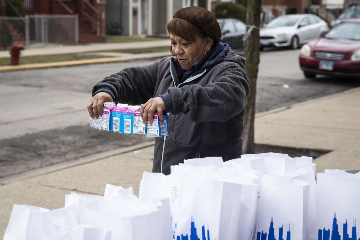 Edith Quinones, the lunchroom manager, packs a bag of three days of free breakfast and lunch meals for students at William P. Nixon Elementary School, 2121 N. Keeler Ave., March 19, 2020.