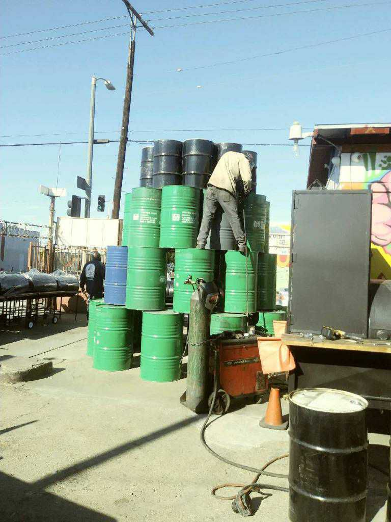 Jose Diaz constructing a Christmas tree from discarded oil barrels in Los Angeles, California