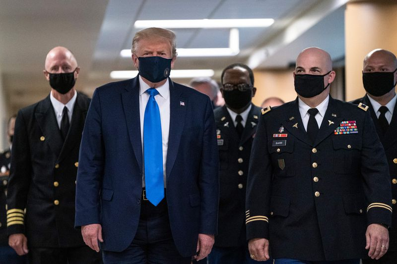 The president walking and wearing a mask surrounded by others, also in masks.