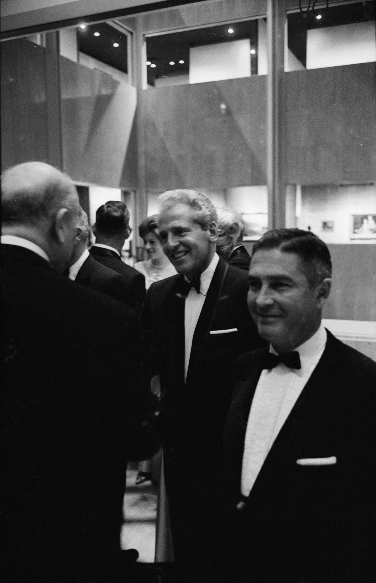 A black and white image of smiling white men in tuxedos.