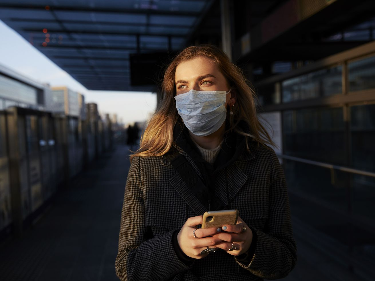 A person wearing a breathing mask holds a cellphone while standing on a city street.