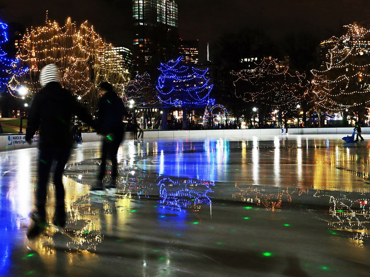 People ice-skating at night, surrounded by illuminated trees.