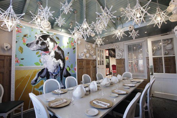 a dining room with a painting of a dog on the wall