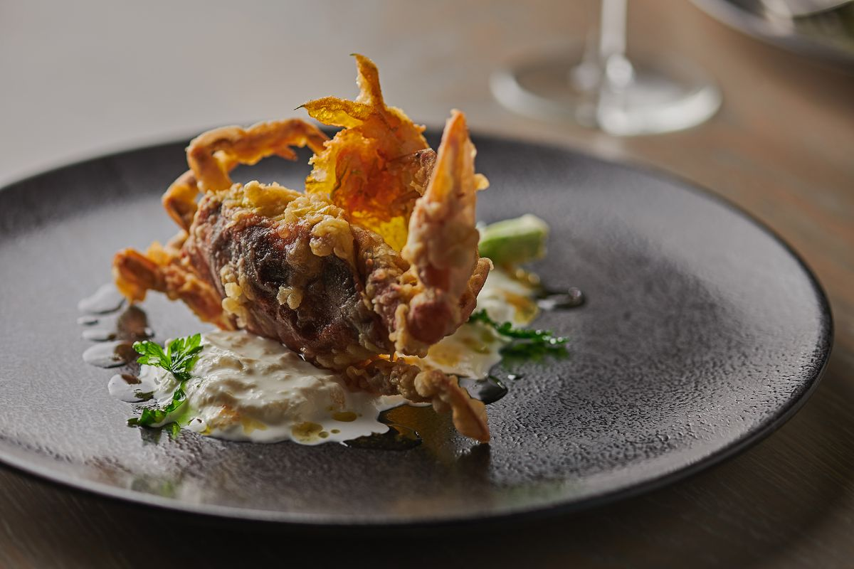 A delicate fried soft shell crab on a round black plate