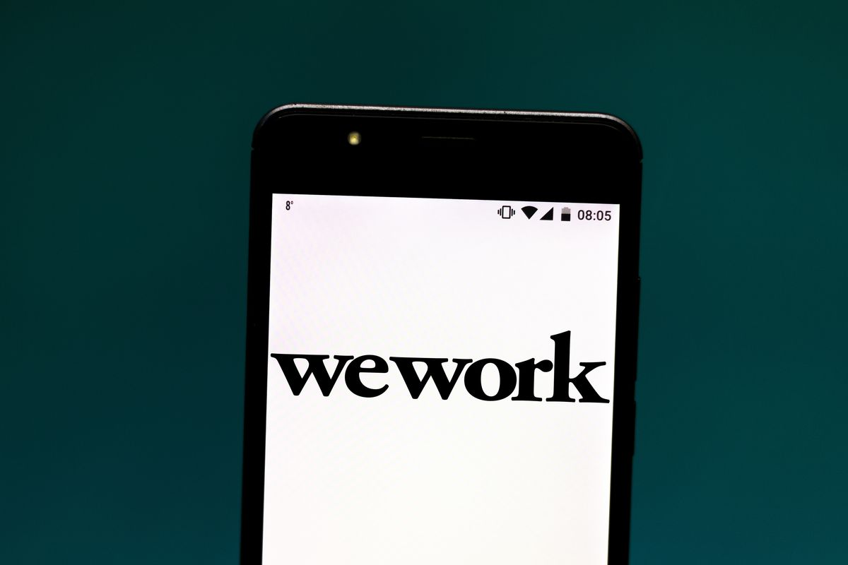Photo illustration a WeWork logo seen displayed on a smartphone.