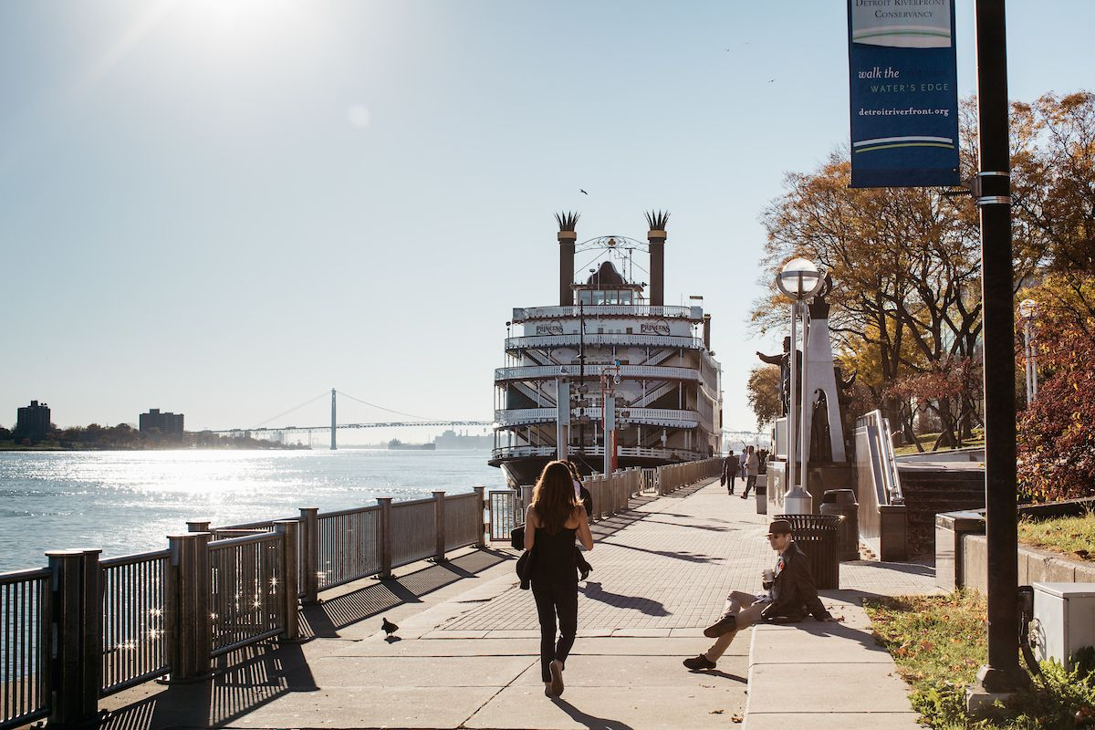 A woman walks on a cement path along the river. Behind her is a ferry boat and in the distance is a blue bridge.