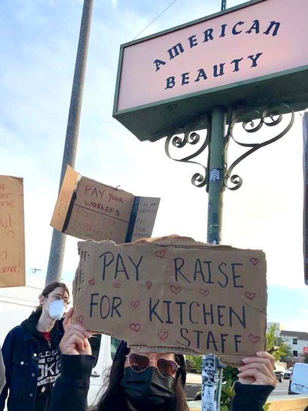 """An American Beauty server protesting outside the Venice restaurant on March 19, 2021 holding a sign that says """"pay raise for kitchen staff."""""""