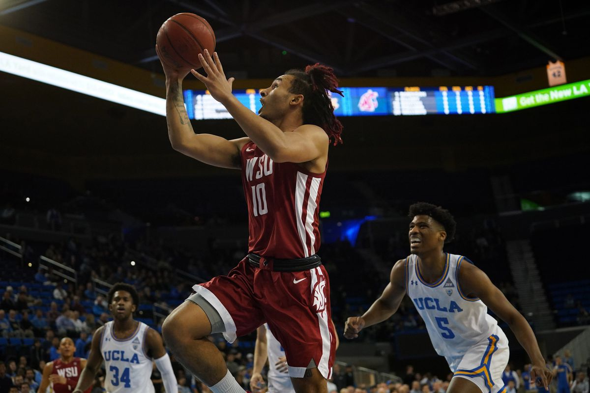 Washington State Cougars guard Isaac Bonton is defended by UCLA Bruins guard Chris Smith in the first half at Pauley Pavilion.