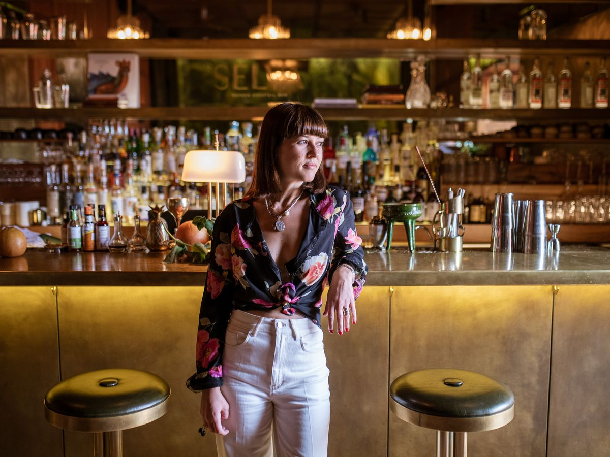 A woman in a blouse and white pants stands in front of a bar.