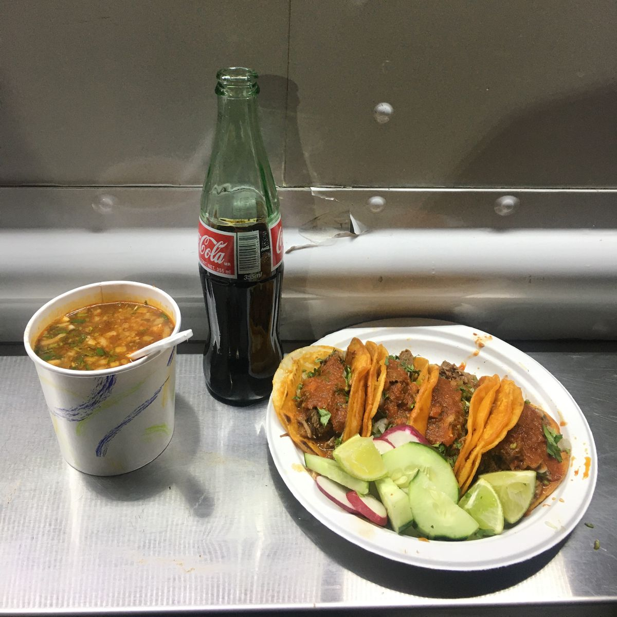 Four birria tacos made with beef, a tall cup of consomme, and a Coca-cola on a metal table