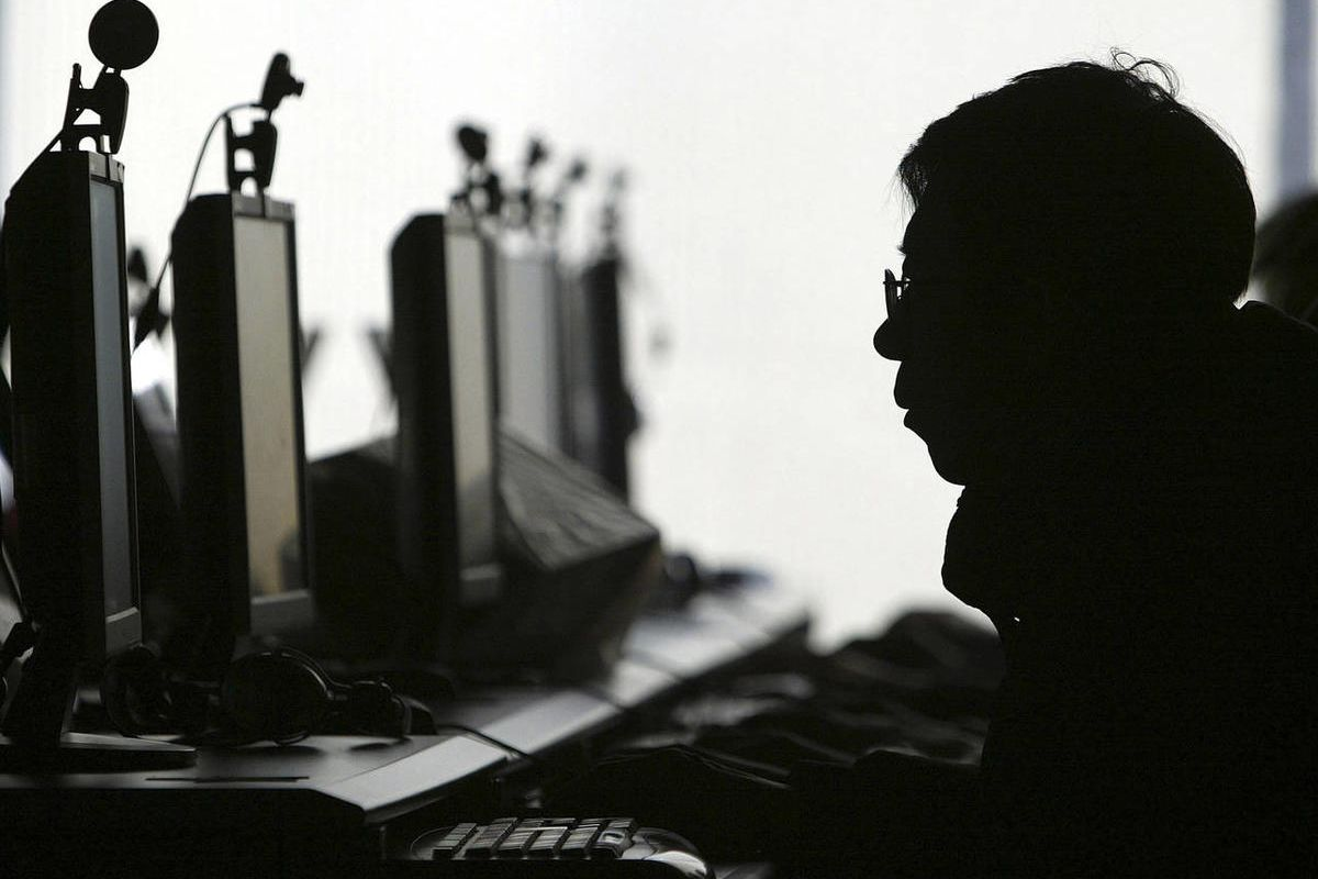 In this Jan 23, 2008 file photo, a computer user is silhouetted with a row of computer monitors.
