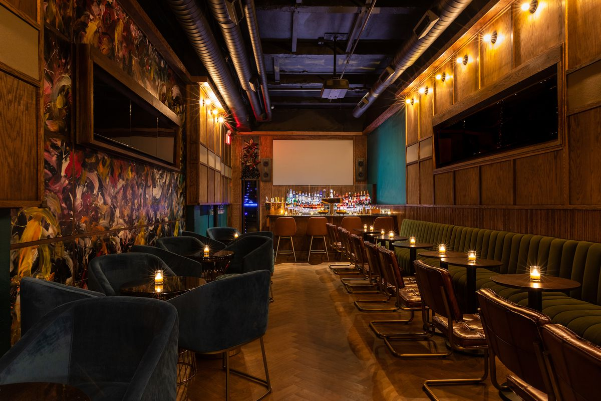 A dimly lit room with wood paneled, sets of television screens hang on either sides of the wall. There's a row of wooden tables with candles on them and a continuous green couch.