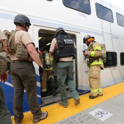 """First responders check out a FrontRunner train during """"Hell on Wheels,"""" a full-scale, two-day, emergency protection and response drill at the Salt Lake Central Station on Tuesday, Aug. 8, 2017. The drill included emergency personnel from the Utah Transit Authority, the FBI, Salt Lake County Emergency Management, the West Valley and Salt Lake City fire departments, University of Utah Emergency Management, the University of Utah Police Department, Amtrak, Union Pacific, Murray Victim Advocates and Utah State Medical Examiner's Office. The drill simulated multiple terrorists entering the Salt Lake Valley and dividing up."""