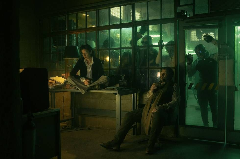 Two members of the Doom Patrol sit in a darkened room together while others press up against the outside of the glass wall behind them in Doom Patrol season 3
