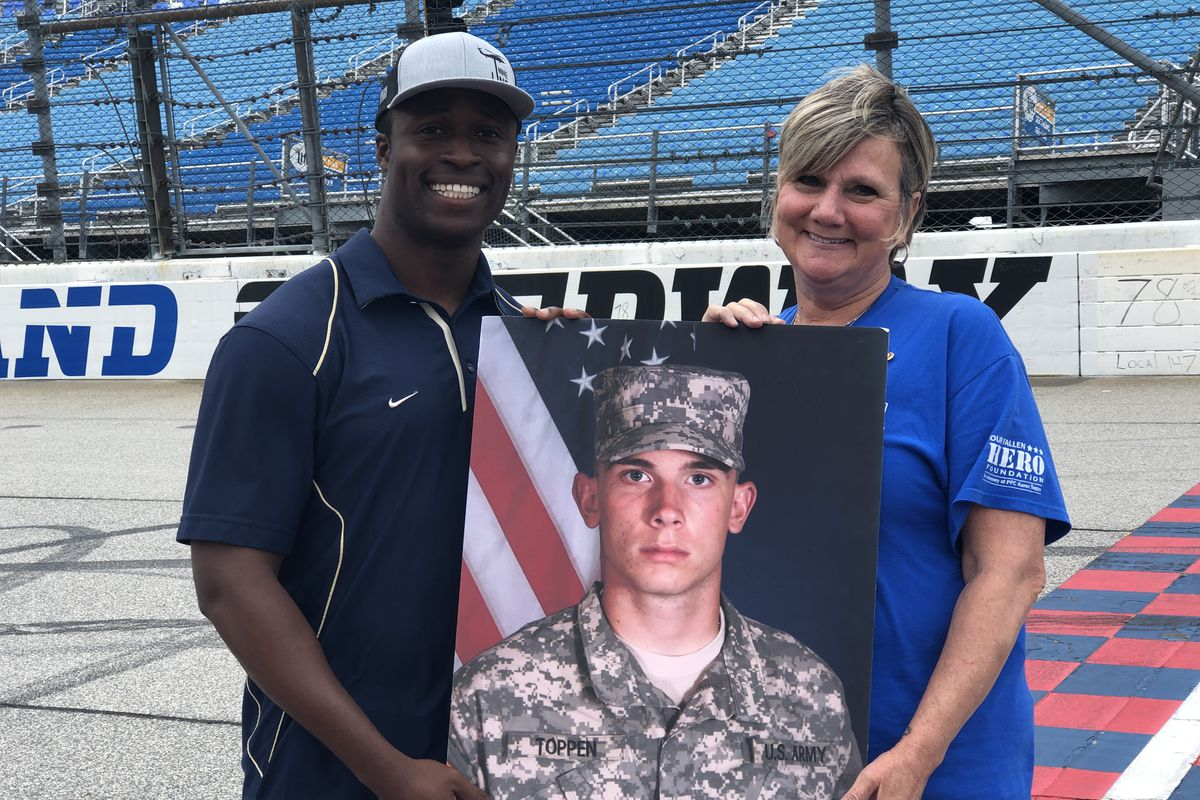 Jesse Iwuji and Pam Toppen, Army Pvt. Aaron Toppen's mother, hold a picture of Aaron.
