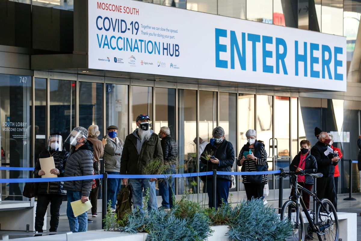 People stand in line at the mass vaccination site at San Francisco's Moscone Convention Center.