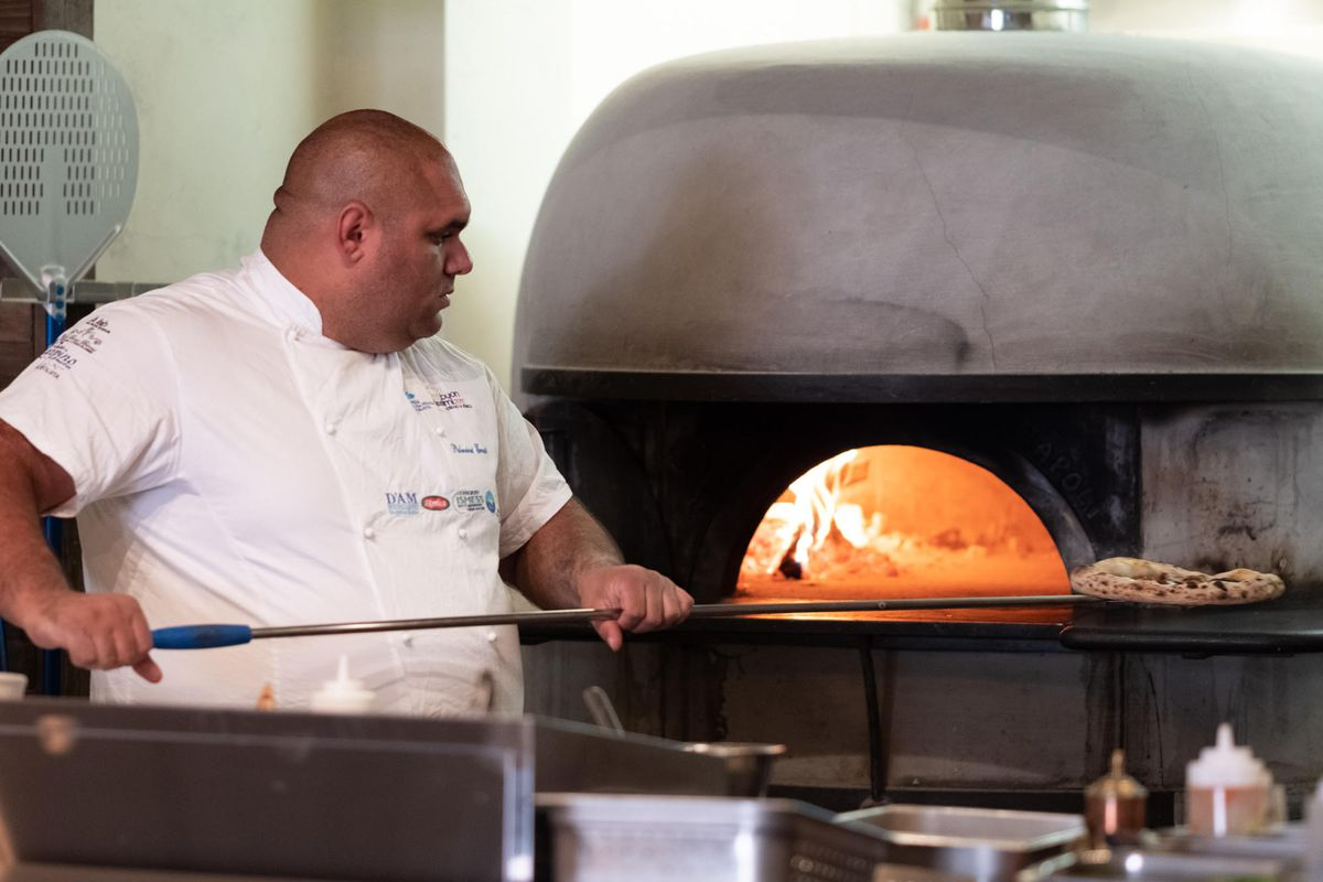 Chef Ernesto Palmieri poses with a pizza