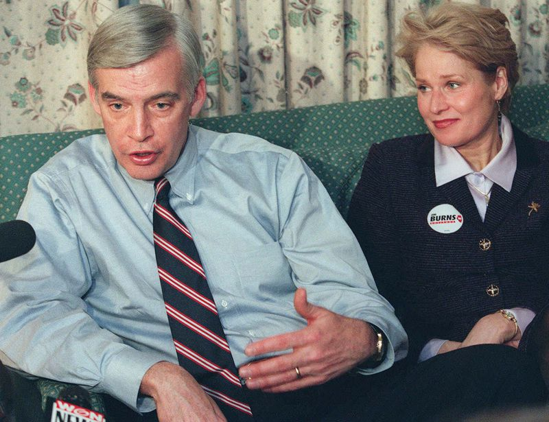 Gubernatorial hopeful Jim Burns on Election Night in March 1998, talking to reporters in his hotel suite. Next to him is his wife, Marty.