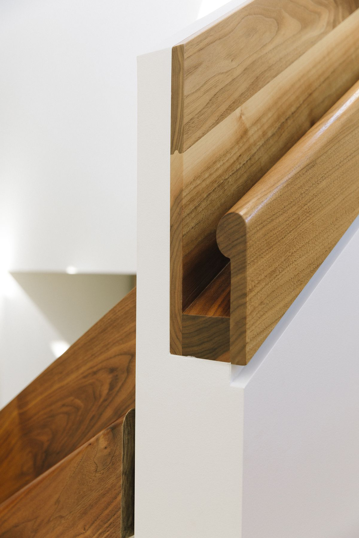 A wooden bumper on a painted white wall.