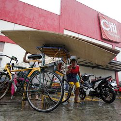 Joel Reyes, loads plywood onto his bicycle after a visit to a hardware store in Tacloban, Friday, Nov. 22, 2013. This hardware store was the first to open following a typhoon.