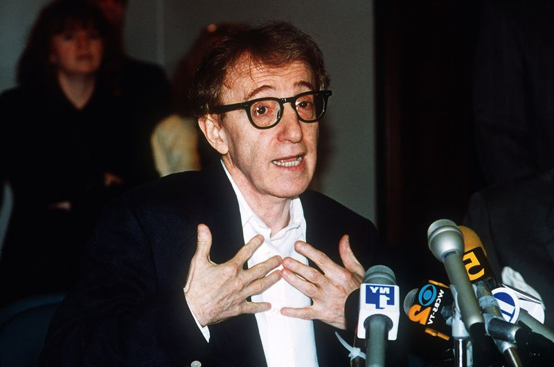 Woody Allen stands before a podium covered in microphones, speaking and gesturing to himself.