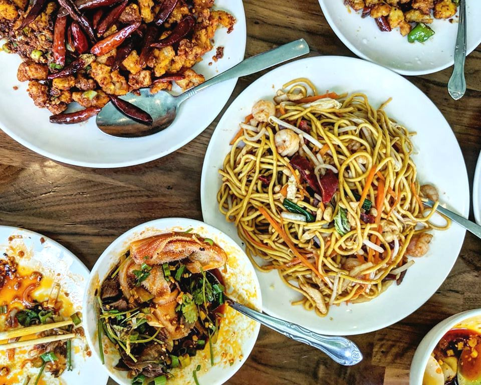 Overhead shot of a table of Chinese food, including lo mein, fried chicken, spicy wontons, and more