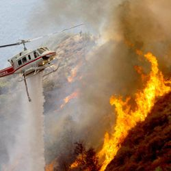 A Los Angeles County Firefighter helicopter drops water on a wildfire burning through 3,600 acres of the Angeles National Forest on Tuesday Sept. 4, 2012 near Glendora, Calif. It could be a week before firefighters can contain the blaze because of high temperatures and rugged terrain in thick brush that hasn't burned in a couple of decades.