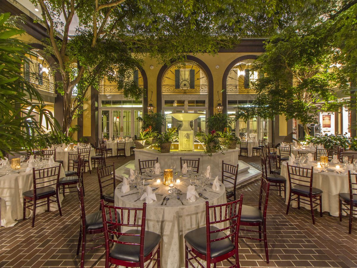 Tables covered with white cloths and floral arrangement are centered around a large fountain in a brick courtyard with many trees.