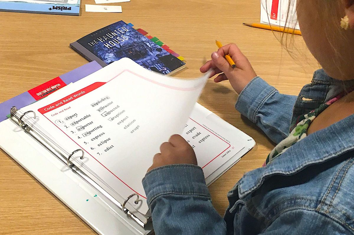 """An ALLIES student goes over a worksheet on words starting with the letter """"e"""" during her Take Flight therapy session."""
