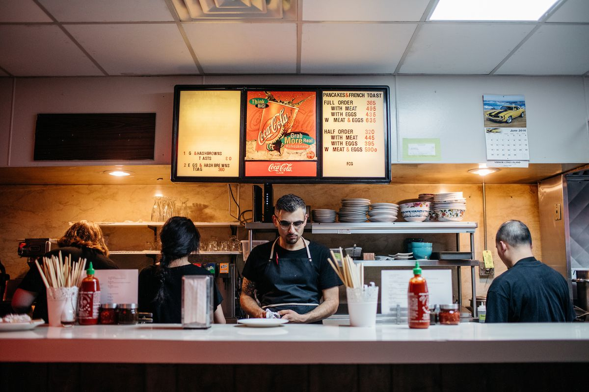 behind the counter, coney island menu in background
