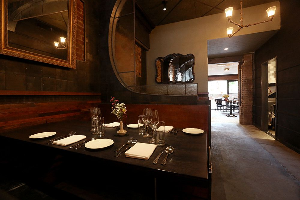 A dark restaurant interior displaying a neatly set table