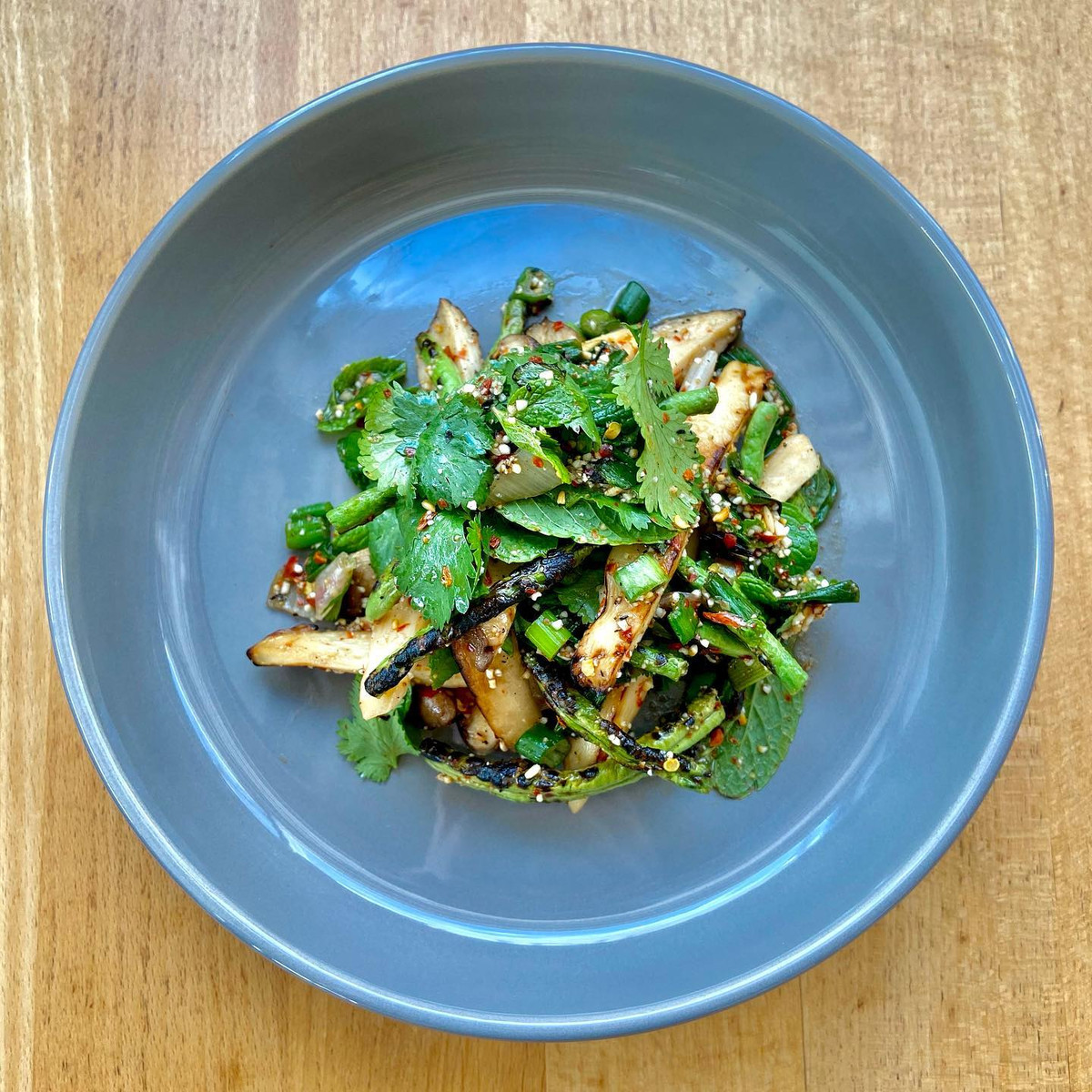 A bowl of eggplant topped with herbs and chili