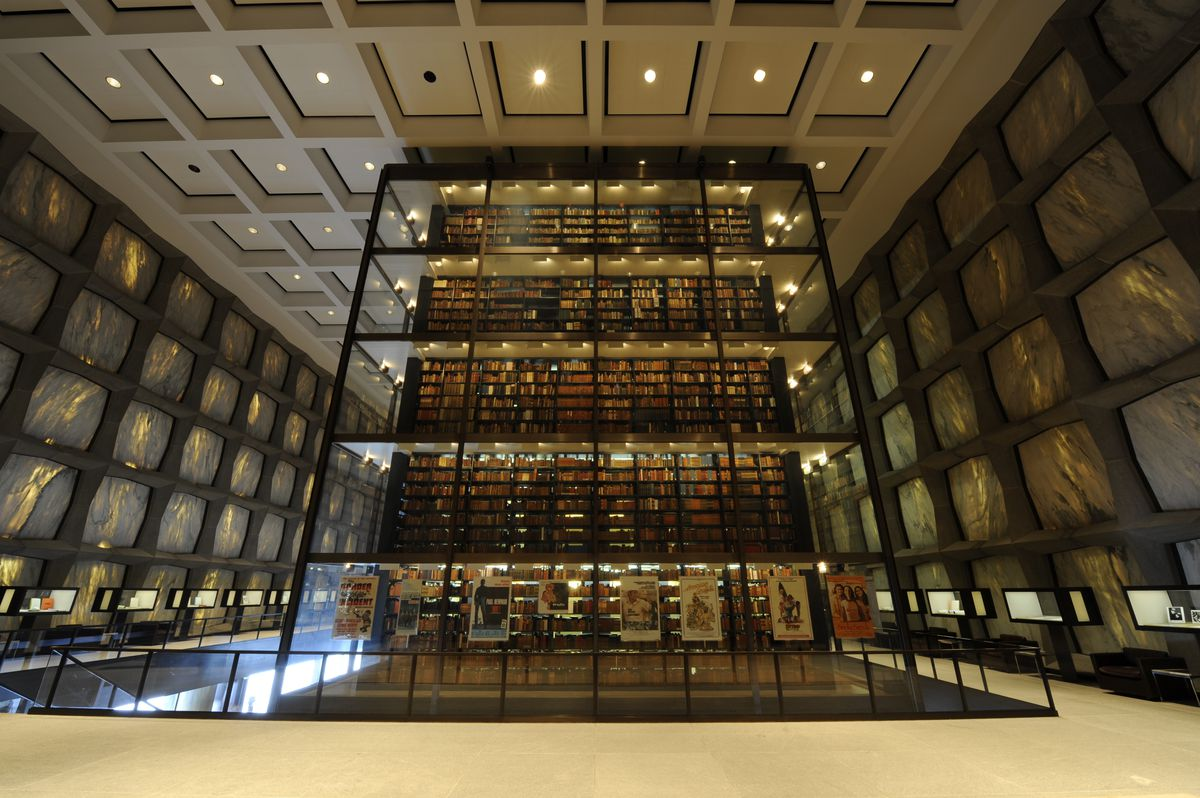 The interior of the Beinecke Rare Book and Manuscript Library in Connecticut. There is a glass tower of bookshelves with many books.