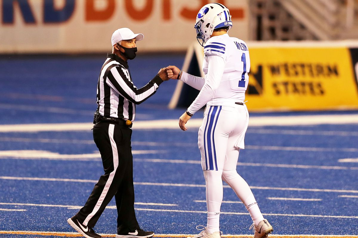 BYU Cougars quarterback Zach Wilson (1) fist-bumps with an official prior to BYU and Boise State playing a college football game at Albertsons Stadium in Boise on Friday, Nov. 6, 2020.